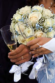 Bride and groom holding hands at wedding glasses — Stock Photo