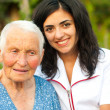 Smiling elderly woman outdoors with doctor / nurse — Stock Photo