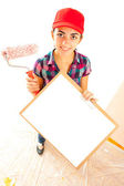 Woman painter with roll brush and clipboard — Stock Photo