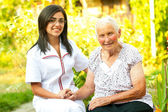 Caring doctor with happy elderly lady — Stock Photo