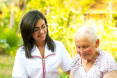 Helping elderly woman outdoors — Stock Photo
