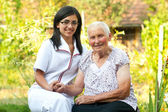 Caring doctor with elderly woman — Stock Photo