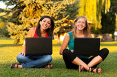 Laughing girls outdoors with laptop — Stock Photo