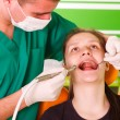 Young male dentist working, treating a young female patient. — Stock Photo #14030281