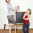 A happy teacher helping her student to calculate. — Stock Photo #14030999