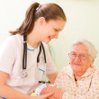 A young doctor, nurse visiting an elderly sick woman holding her hands with caring attitude. — Stock Photo