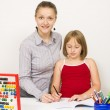 A teacher and a student learning together in the school, colored pencils on a blue recipient against white wall — Stock Photo