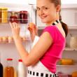 Stock Photo: A young woman using the refrigerator, reaching for eggs. Food, milk, red wine and juice in the background.