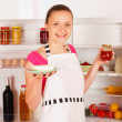 Foto Stock: A young woman with jam and butter in her hand in front of the open refrigerator. Food, milk, red wine and juice in the background.