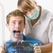 A dentist and her patient posing with funny facial expression. — Stock Photo