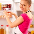 A young woman using the refrigerator, reaching for eggs. Food, milk, red wine and juice in the background. — Stock Photo