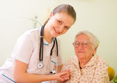 Nurse visiting an elderly sick woman holding her hands with caring attitude. — Stock Photo