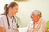 Nurse visiting an elderly sick woman socialising - talking - with her. — Stock Photo