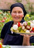 Elderly woman with fresh food — Stock Photo