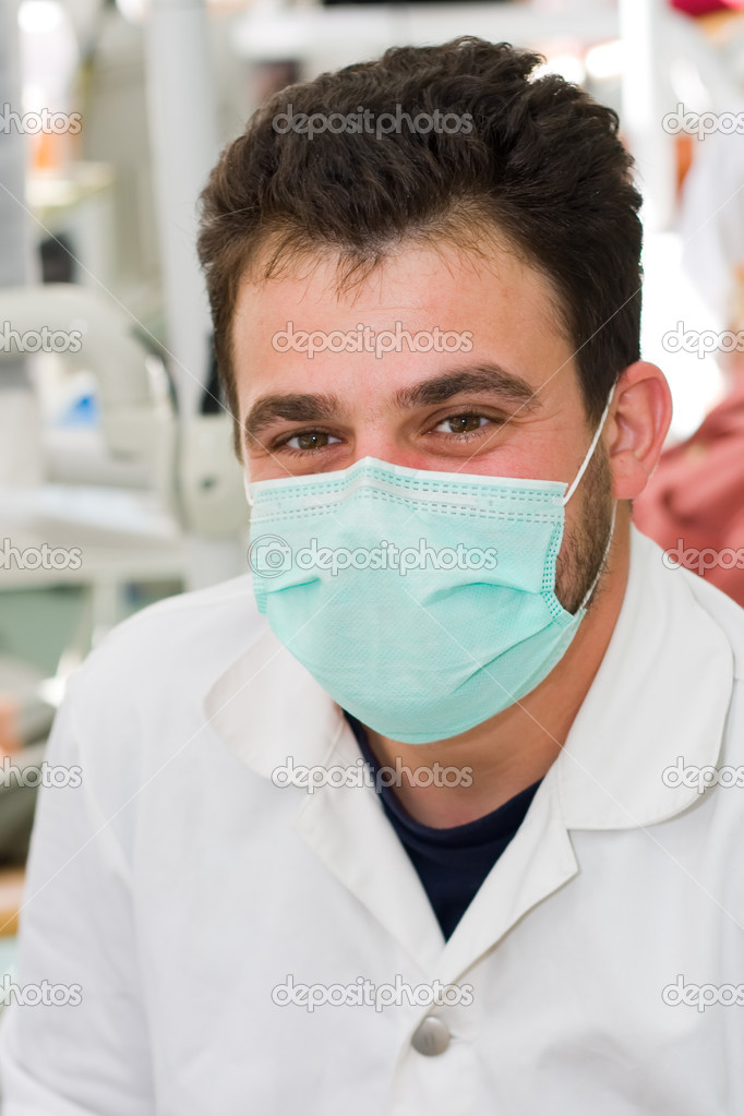 A young male dentist smiling at workplace - part of a series. — Stock Photo #14034321