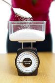 Sugar in kitchen scale — Stock Photo