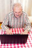 Old man using technology — Stock Photo