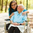 Woman in Wheelchair and a Nurse - Stock Photo
