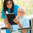 Elderly Lady in Wheelchair Reading — Stock Photo