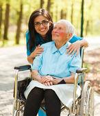Mujer en silla de ruedas y una enfermera — Foto de Stock