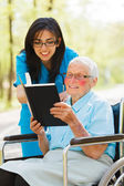 Signora anziana nella lettura di sedia a rotelle — Foto Stock