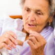 Stock Photo: Elderly lady taking pills