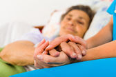 Caring nurse holding hands — Stock Photo