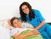 Nurse caring for elder patient — Stock Photo