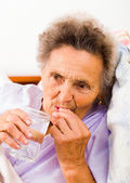 Elderly lady taking pills — Stock Photo