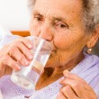 Stock Photo: Senior womtaking supplements