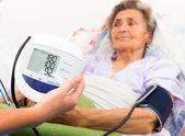 Nurse using digital blood pressure measure — Stock Photo