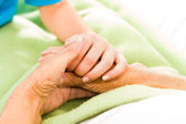 Nurse holding patient hands — Stock Photo