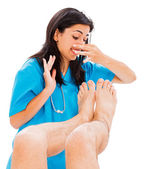 Doctor defending herself from stinky man feet — Stock Photo