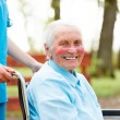 Smiling elderly lady in wheelchair — Stock Photo