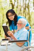 Anciana en la lectura de la silla de ruedas — Foto de Stock