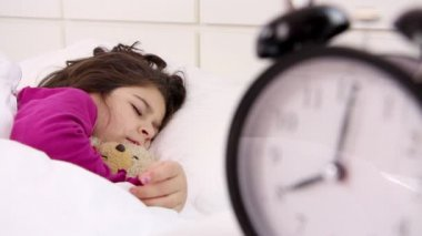 Little girl wakes up, alarm clock close up — Stock Video