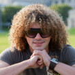Royalty-Free Stock Photo: Portrait of young smiling guy with curly hair with sunglasses