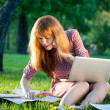 Woman on the grass with notebook and paper — Stock Photo