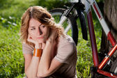 Girl sits with a bicycle — Stock Photo