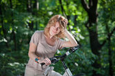 Girl stay with a bicycle — Stock Photo