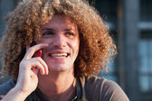 Young guy with curly hair talk on cellphone — Stock Photo