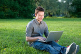Man on the grass with notebook — Stock Photo