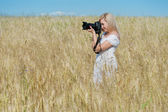 Beautiful woman take a photo with camera in a field — Stock Photo
