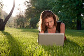 Woman with laptop on the grass — Stock Photo