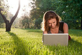 Woman sits on the grass with laptop — Stock Photo