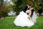 Newly married couple dancing in field — Stock Photo