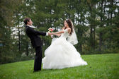 Newly married couple dancing in field — Photo