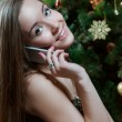 Woman near Christmas tree making phone call - Stock Photo
