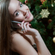 Woman near Christmas tree making phone call — Stock Photo