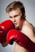 Fighting blond man with boxing glove — Stock Photo